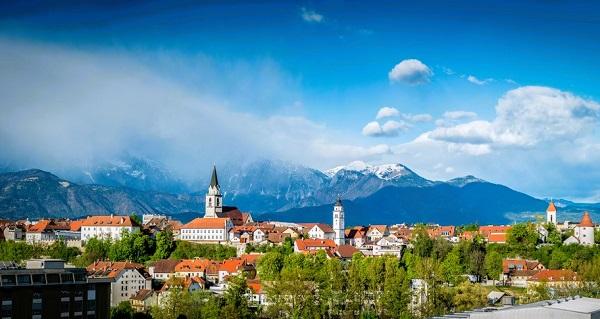 Het uitzicht van de stad Kranj met onder meer de klokkentoren van Svei Kancijan & op de achtergrond de besneeuwde bergtoppen