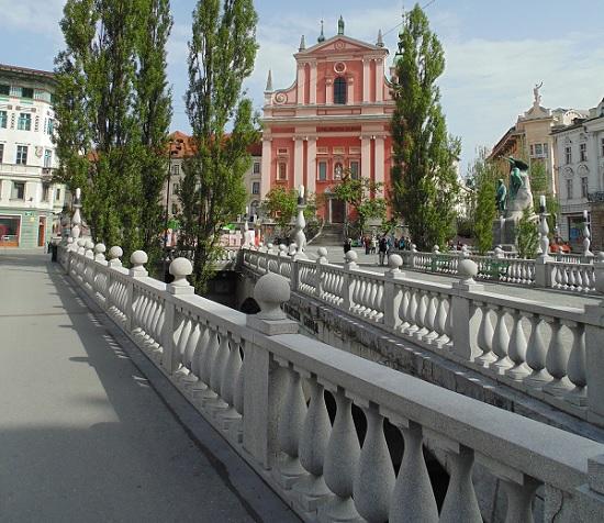 Een blik op de Drie Bruggen met op de achtergrond de Barokke Franciscuskerk en het standbeeld van France Prešeren