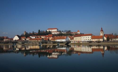 Het stadspanorma van Ptuj, met aan de rechterkant de Georgiuskerk & op de voorgrond de rivier de Drava & de brug
